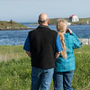 Rear view of couple taking picture with camera at riverbank, Cape Breton Island, Nova Scotia, Canada
