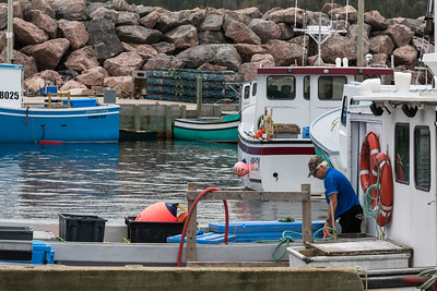 Senior male fisherman on fishing boat at harbor, Neil's Harbour, Cape Breton Island, Nova Scotia, Canada