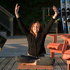 Woman doing yoga on an outdoor deck, Lake of The Woods, Ontario, Canada