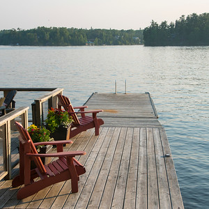 Adirondack chairs on a dock at the lakeside, Lake of The Woods, Ontario, Canada