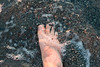 Human foot in water on the beach, Trout River, Gros Morne National Park, Newfoundland and Labrador, Canada