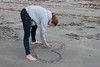 Girl drawing heart in sand on beach, Shallow Bay, Gros Morne National Park, Newfoundland and Labrador, Canada