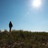 Girl standing on grassy sand dune under bright sunshine at Cavendish Dunelands Trail, Green Gables, Prince Edward Island, Canada