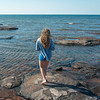 Girl standing on rocks along Cavendish Beach, Green Gables, Prince Edward Island, Canada