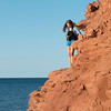 Girl standing on cliff overlooking Atlantic Ocean, Green Gables, Cavendish, Prince Edward Island, Canada