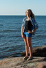 Girl standing on rock overlooking Atlantic Ocean, Cavendish Beach, Green Gables, Prince Edward Island, Canada