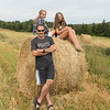 Man with his daughters on hay bale at farm, Kensington, Prince Edward Island, Canada