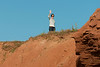 Woman waving from top of rocky cliff, Green Gables, Cavendish, Prince Edward Island, Canada