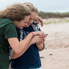 Girls watching smartphone on the beach, York Point, Prince Edward Island, Canada