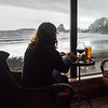 Woman sitting in a restaurant at seaside, Cox Bay, Pacific Rim National Park Reserve, British Columbia, Canada