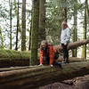 Girls climbing on a log in forest, Cathedral Grove, Vancouver Island, British Columbia, Canada