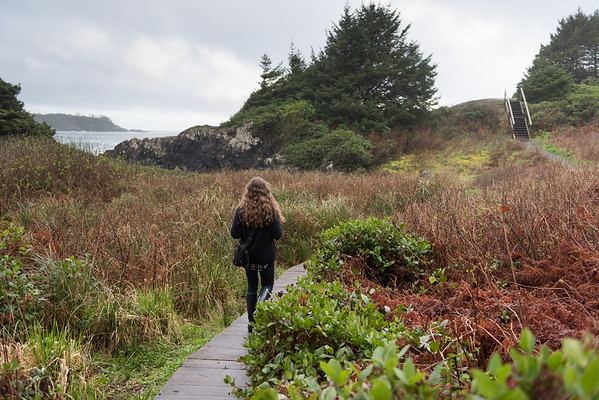 Girl walking on boardwalk at coast, Cox Bay, Pettinger Point, Pacific Rim National Park Reserve, Tofino, British Columbia, Canada