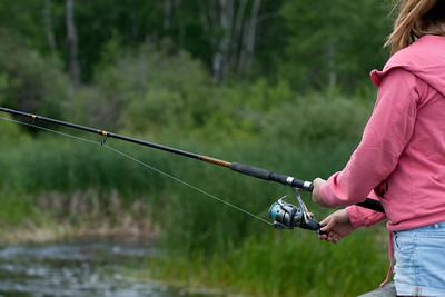 Mid section view of a girl fishing, Riding Mountain National Park, Manitoba, Canada