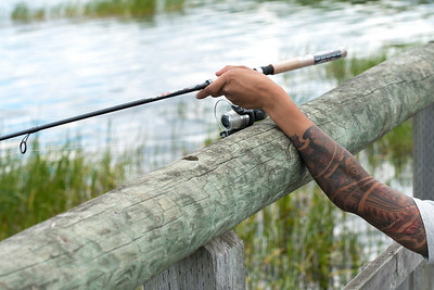 Closeup of a person's arm holding a fishing rod, Riding Mountain National Park, Manitoba, Canada