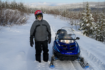 Man standing near snowmobile, Sun Peaks Resort, Sun Peaks, British Columbia, Canada