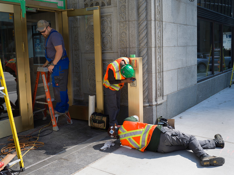 Manual workers repairing door of building, Toronto, Ontario, Canada