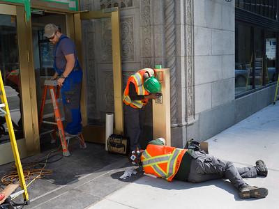 Manual workers repairing door of building, Toronto, Ontario, Canada