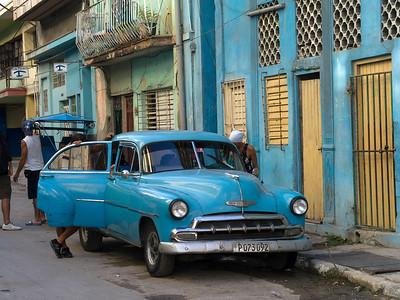 People standing near a car parked outside building, Havana, Cuba