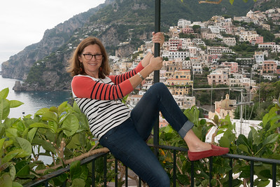 Happy woman sitting on the railing of a balcony, Positano, Amalfi Coast, Salerno, Campania, Italy