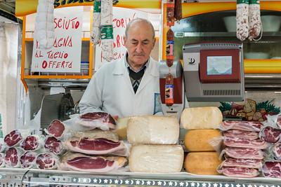 Butcher at his shop's counter, Orvieto, Terni Province, Umbria, Italy