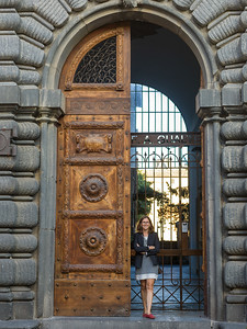 Happy woman standing at arched doorway entrance, Orvieto, Terni Province, Umbria, Italy