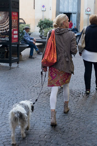 Woman walking with her dog on street, Orvieto, Terni Province, Umbria, Italy