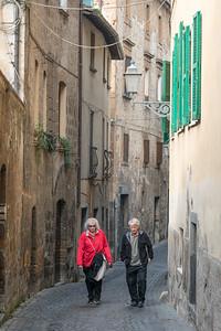 Senior couple walking on an alley, Orvieto, Terni Province, Umbria, Italy