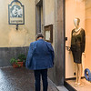 Rear view of a man standing outside of a clothing store, Orvieto, Terni Province, Umbria, Italy