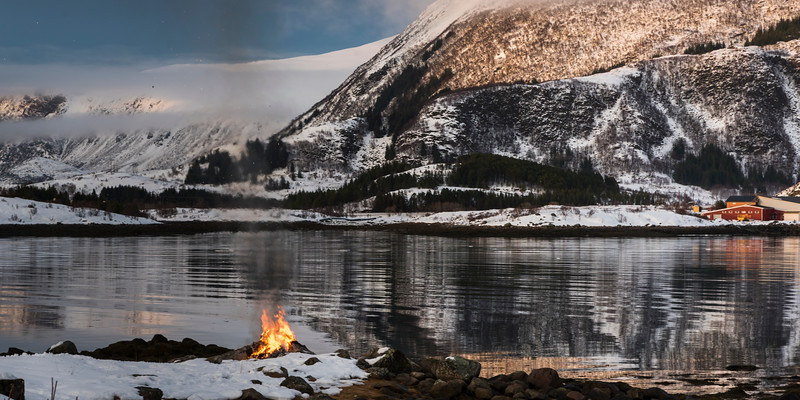 Bonfire at coast with mountain in the background, Lofoten, Nordland, Norway
