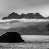 Rock formations in sea with mountain range in the background, Lofoten, Nordland, Norway