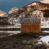 Log cabin at coast with sunlight falling on mountain peak, Lofoten, Nordland, Norway