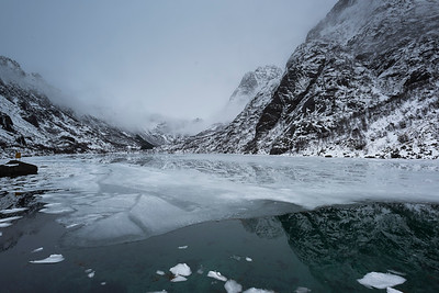 Reflection of mountains with ice floe floating in water, Lofoten, Nordland, Norway