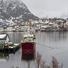 Trawler in sea with fishing village in the background, Lofoten, Nordland, Norway