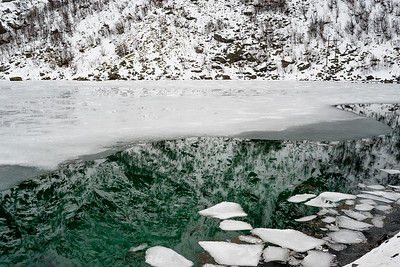 Reflection of mountain with ice flow floating on water, Lofoten, Nordland, Norway