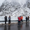 Tourists looking at mountain view from coastal road, Lofoten, Nordland, Norway