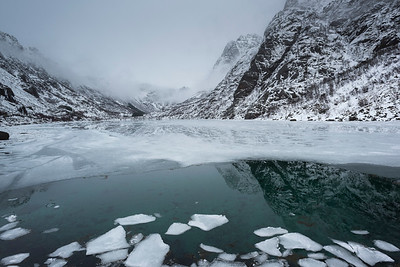 Reflection of mountains with ice floe floating on water, Lofoten, Nordland, Norway