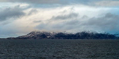 Sea with mountain in the background against cloudy sky, Norway