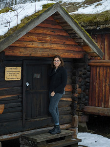 Woman standing at the entrance of an old log cabin with a sod roof, Norway