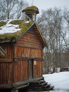 Old log house with a sod roof in snow, Norway