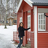 Woman standing at the entrance of a wooden house in snow, Norway