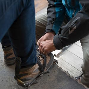 Low section view of men putting on crampon boot, Perito Moreno Glacier, Santa Cruz Province, Patagonia, Argentina