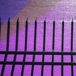 Metal fence by colorful wall, Minneapolis, Hennepin County, Minnesota, USA