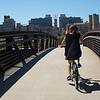 Woman cycling on footbridge in Minneapolis, Hennepin County, Minnesota, USA