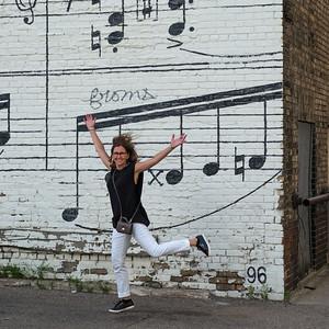 Cheerful woman in front of Schmitt Music Mural, Minneapolis, Hennepin County, Minnesota, USA
