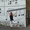 Cheerful woman in front of Schmitt Music Mural, Minneapolis, Hennepin County, Minnesota, USA