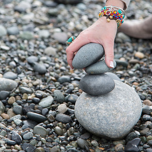 Close-up of a person's hand making stack of stones, Deception Pass State Park, Oak Harbor, Washington State, USA