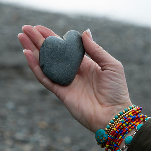 Close-up of a woman's hand holding a heart shaped stone, Deception Pass State Park, Oak Harbor, Washington State, USA