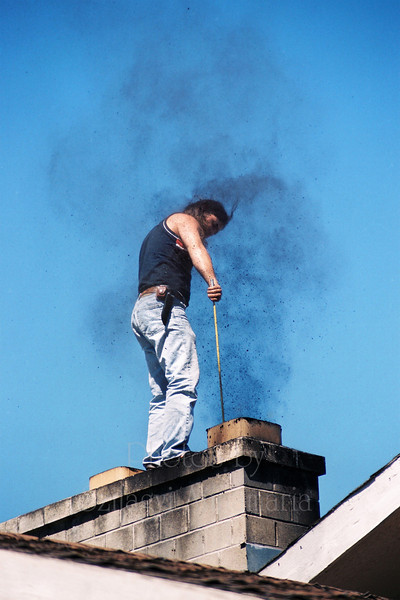 Young man standing on the roof of the house,cleaning the chimney