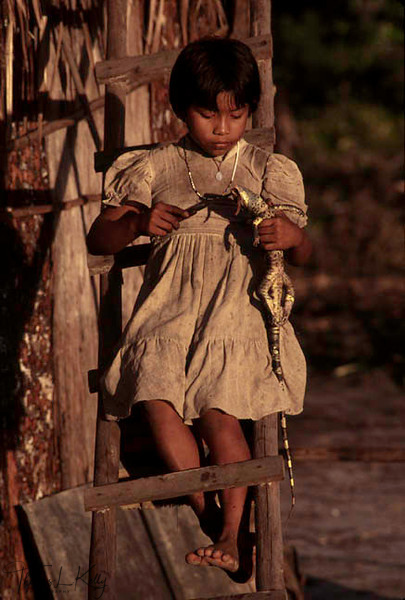 Makuna girl cuts up an iguana for the evening meal. Vaupes Basin, Eastern Colombia Amazon