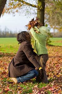 A young mixed race girl playing in the autumn leaves with her black mother